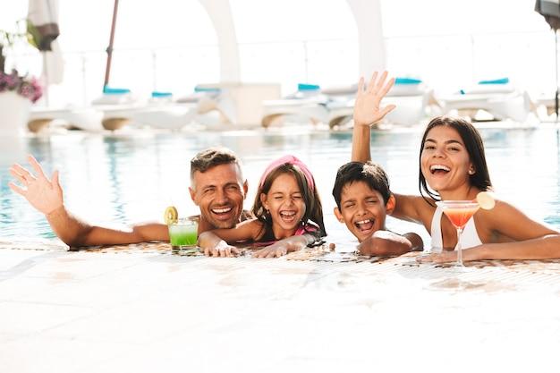 Счастливая молодая семья весело в бассейне