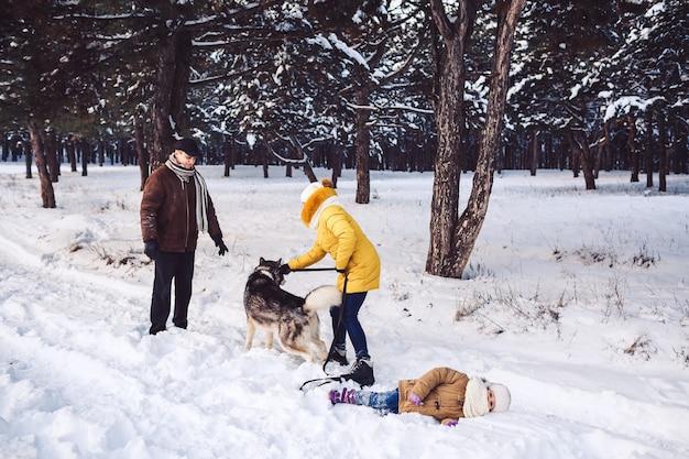 Счастливая молодая семья весело играет с собакой в зимнем парке
