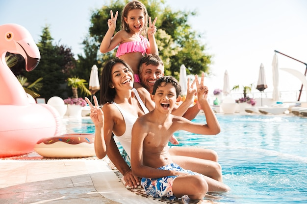 Happy young family having fun together at the swimming pool