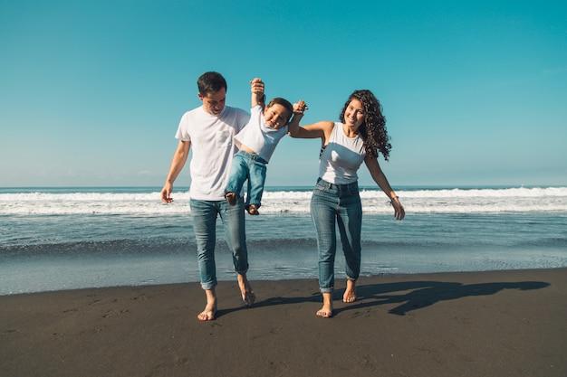 Giovane famiglia felice divertendosi con il bambino sulla spiaggia soleggiata
