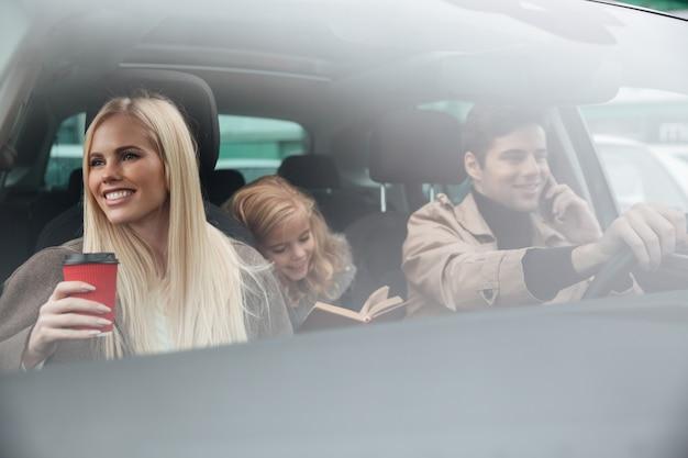 Счастливая молодая семья в машине