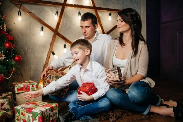 Счастливая молодая семья в рождественских украшениях, мама, папа и маленький мальчик возле елки с подарками рядом