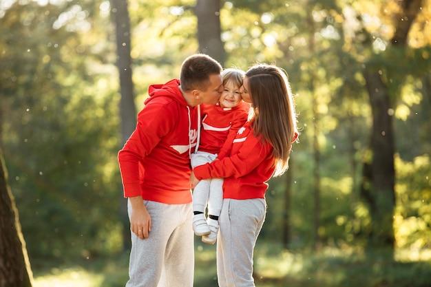 秋の公園で幸せな若い家族。ママと屋外で小さな娘にキスしています。