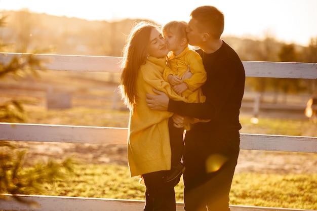 秋の公園で幸せな若い家族。ママとパパが小さな娘を屋外でキスします。