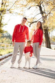 秋の公園で幸せな若い家族。ママ、パパ、小さな娘が屋外で一緒に生活を楽しんでいます。
