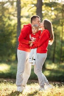 Счастливая молодая семья в осеннем парке. мама, папа и маленькая дочь наслаждаются совместной жизнью на открытом воздухе.