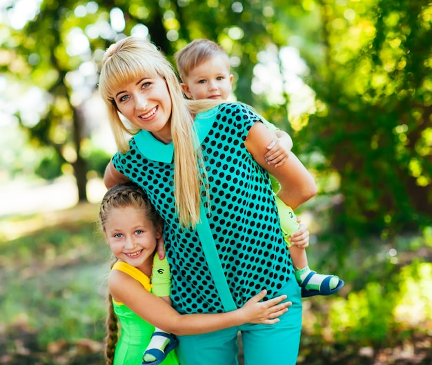 Happy young family, mother and childrens together having fun outdoors on the nature
