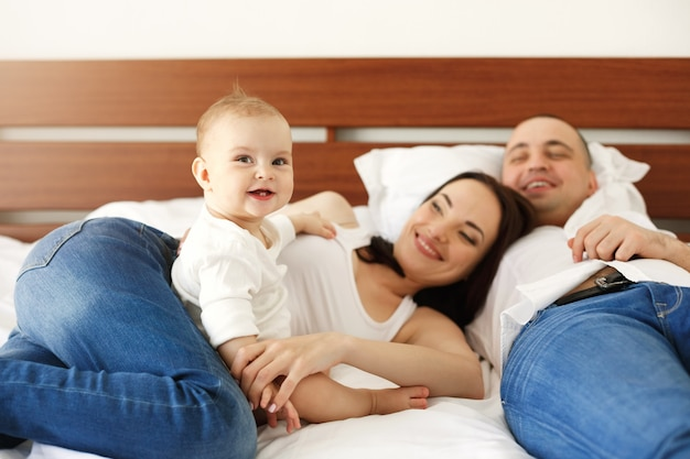 Happy young family of mother father and little baby woman smiling rejoicing lying on bed at home. focus on daughter.