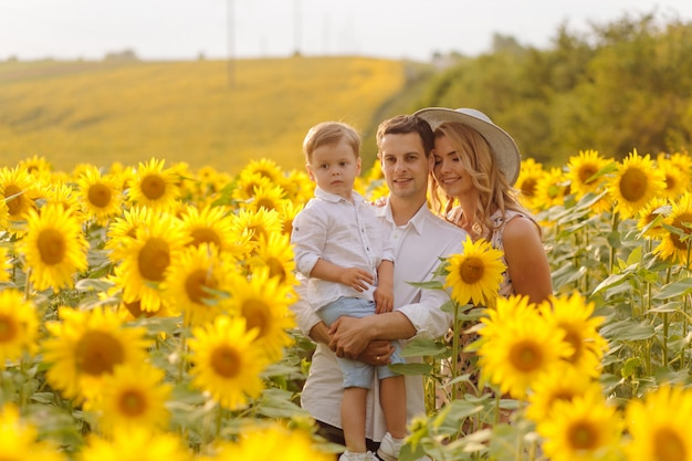 Happy young family, mother father and son, are smiling, holding and hugging in the sunflower field