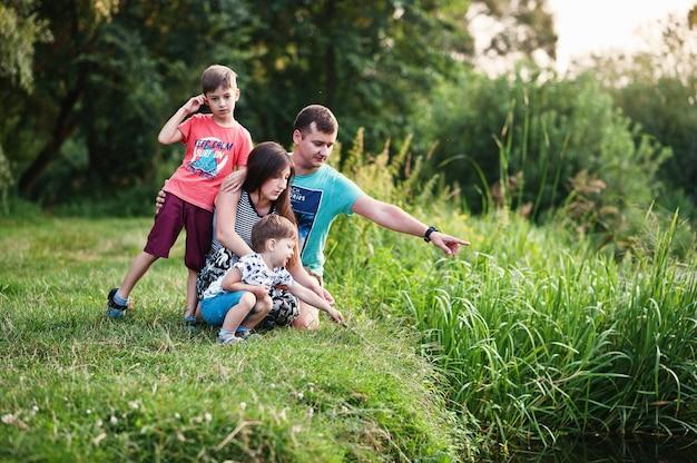 幸せな若い家族:母、父、自然の中で楽しんでいる2人の子供息子。