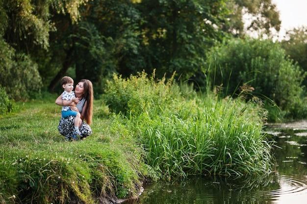 幸せな若い家族:楽しんでいる自然の息子と子供を持つ母親。