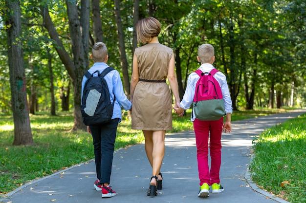 행복 한 젊은 가족, 공원에서 산책하는 두 소년과 어머니. 건강한 라이프 스타일 컨셉