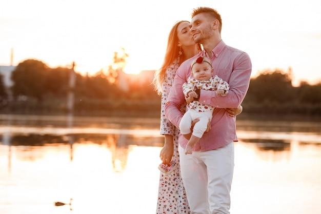湖、池の近くの幸せな若い家族。日没で一緒に生活を楽しんでいる家族。自然を楽しんでいる人。家族の一見。母、父、子供が屋外で自由な時間を過ごしながら笑顔