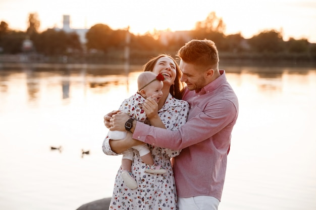 Happy young family near lake, pond. family enjoying life together at sunset. people having fun in nature. family look. mother, father, child smiling while spending free time outdoors