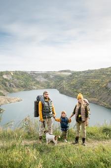 暖かいカジュアルウェアと川沿いや山に立っている間あなたを見ている彼らのかわいい犬の3人の幸せな若い家族