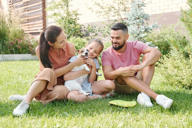 彼らのかわいい犬をpettinf芝生の上に座って裏庭で一緒に時間を過ごす3人の幸せな若い家族