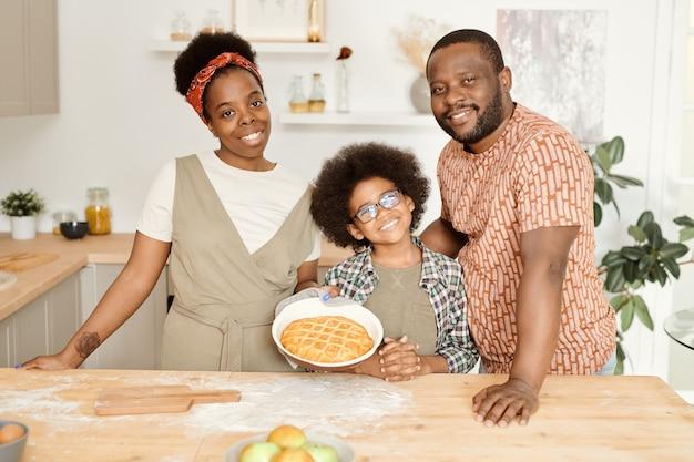 Счастливая молодая семья из трех человек со свежим испеченным яблочным пирогом, стоящим у кухонного стола