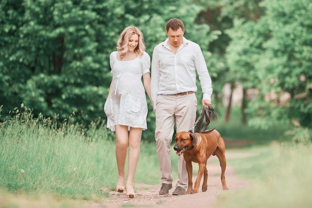 都市公園を散歩して幸せな若い家族。家族の幸せの概念