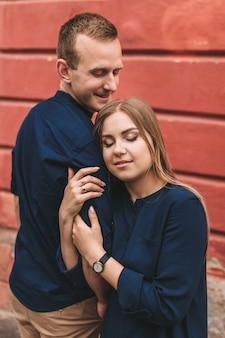 赤い壁の背景に幸せな若い家族。若い女性は彼女の男の肩に頭を置いた