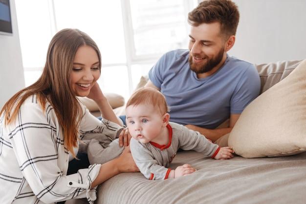 幸せな若い家族。小さな子供を楽しんでいる両親