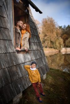 大きな木造住宅の窓から覗く幸せな若い家族。家族のために家を買う、家を借りる、という概念