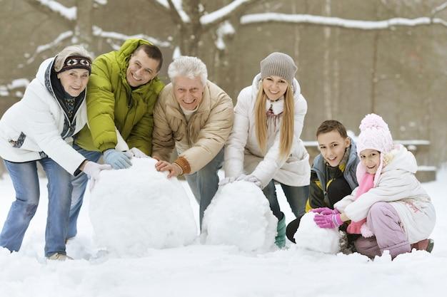 自然の中で屋外の美しい晴れた冬の日に新雪で遊んで雪だるまを構築する幸せな若い家族