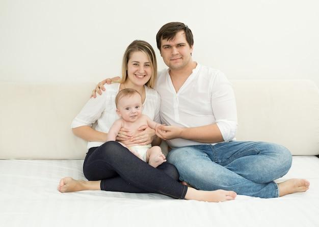 침대에 아기 아들과 함께 포즈를 취하는 행복한 젊은 가족
