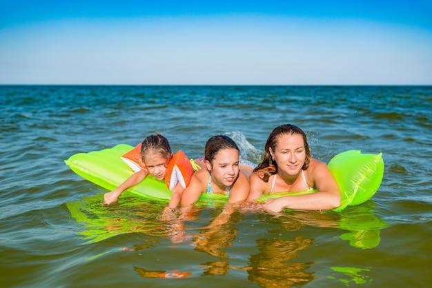 幸せな若い家族のポジティブなママと2人の小さな娘は、休暇中の晴れた夏の日に海の黄色いエアマットレスで泳ぐ