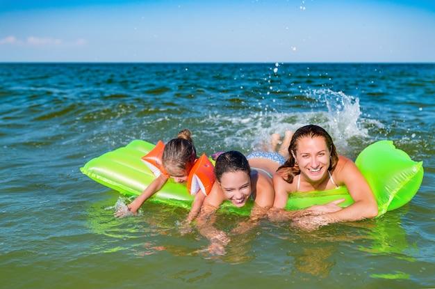 Счастливая молодая семья, позитивная мама и две маленькие дочери плавают на желтом надувном матрасе в море