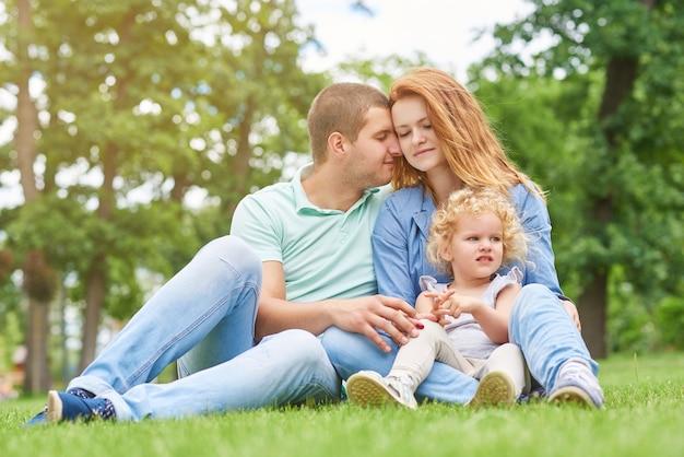 公園でリラックスして幸せな若い家族