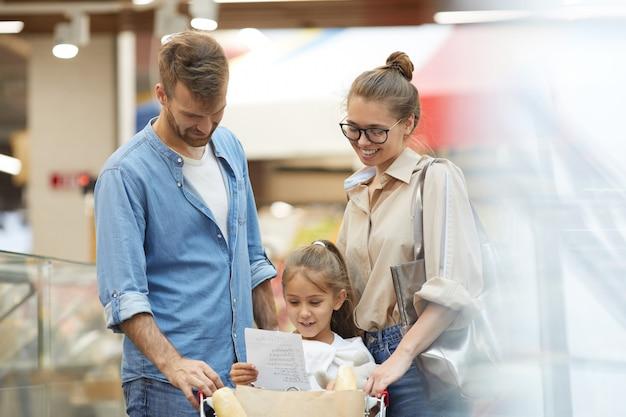 Счастливая молодая семья, делающая покупки в супермаркете