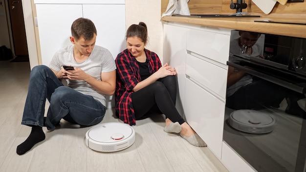 幸せな若い家族は、キッチンのスマートフォンで木の床から汚れを取り除く現代のロボット掃除機を制御する床に座っています