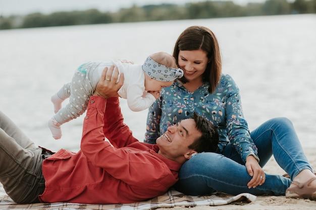 水の近くに座って幸せな若い家族