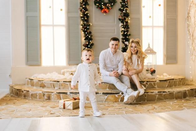 Счастливая молодая семья сидит на крыльце дома, украшенного к рождеству