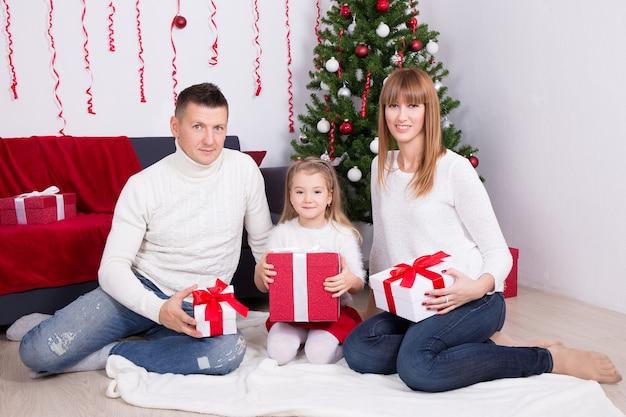 クリスマスツリーの前にギフトボックスと一緒に座って幸せな若い家族