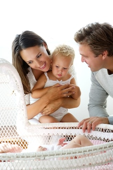 Happy young family smiling at baby in cot