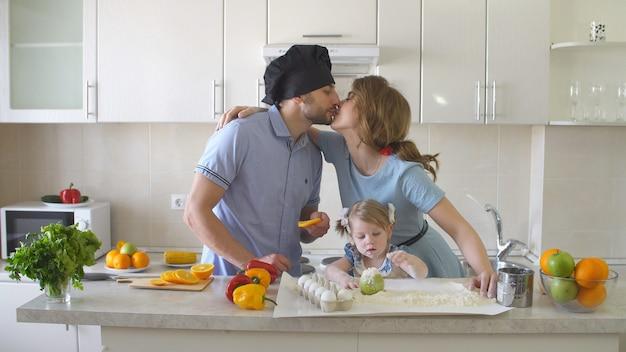 幸せな若い家族が台所で時間を過ごします。