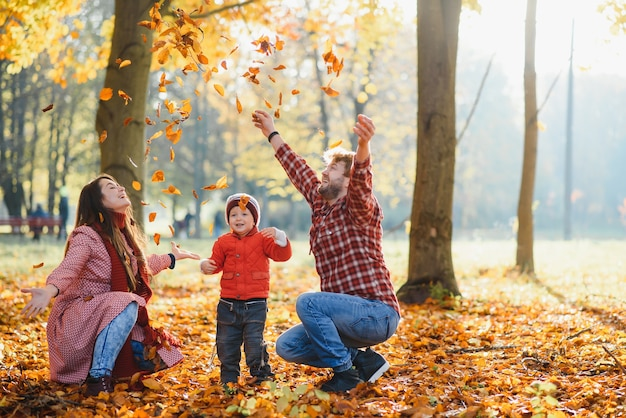 Счастливая молодая семья, проводящая время на открытом воздухе в осеннем парке