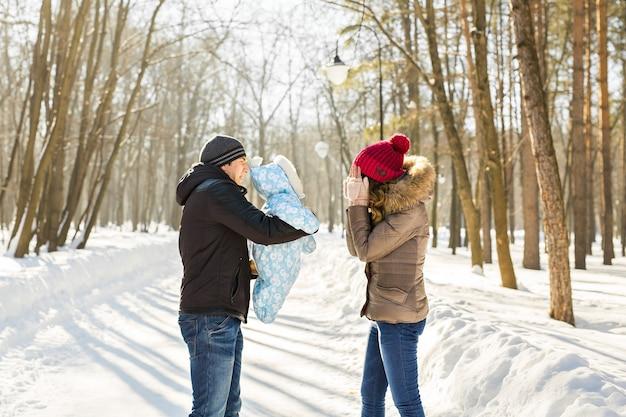 Счастливая молодая семья, проводящая время на открытом воздухе зимой.