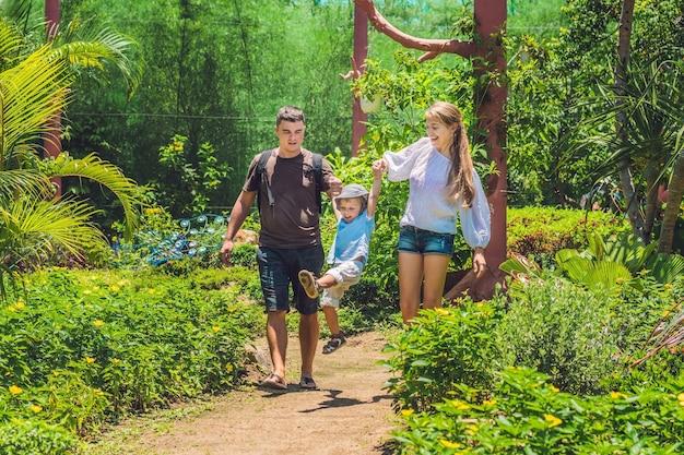 Счастливая молодая семья проводит время на открытом воздухе в летний день