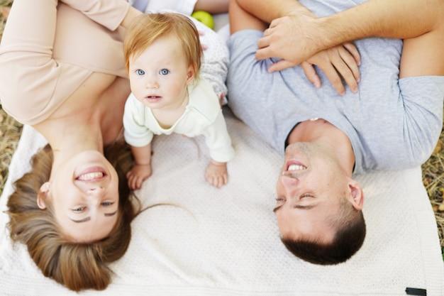 행복한 젊은 가족이 함께 시간을 보내고, 어머니와 아버지는 푸른 자연 속에서 아기를 안고 있습니다.