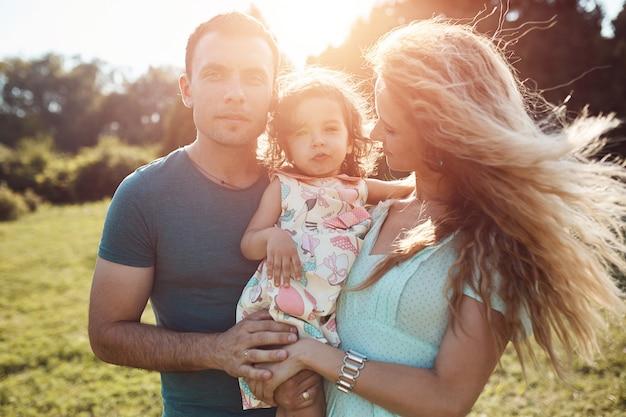 Счастливая молодая семья проводя время совместно снаружи в зеленой природе.