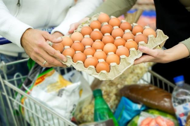 スーパーマーケットで卵とカウンターの近くに立っている幸せな若い家族