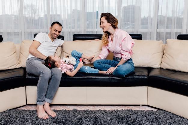 집에 머물고 행복 한 젊은 가족. 부드러운 순간을 즐기는 가족,