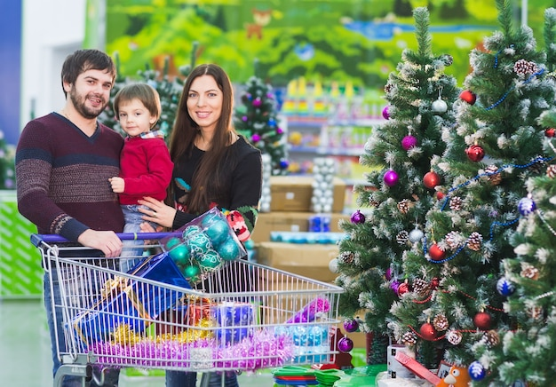 Happy young family in the supermarket chooses gifts for christmass