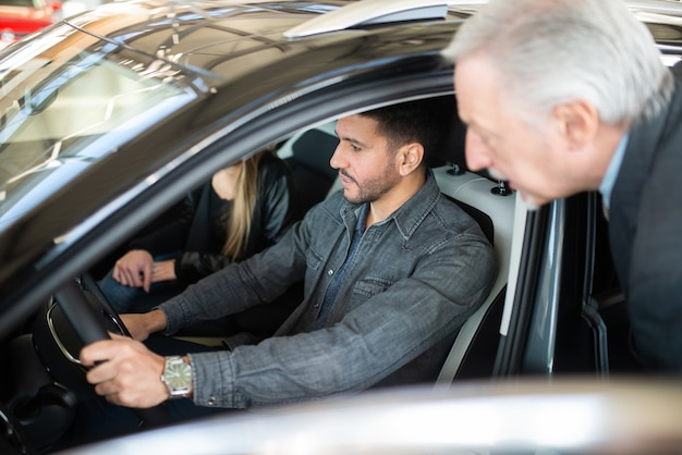 판매원과 이야기하고 쇼룸에서 새 차를 선택하는 행복한 젊은 가족
