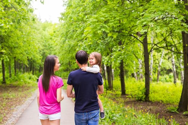 緑の自然の中で外の道を歩いて幸せな若い家族。