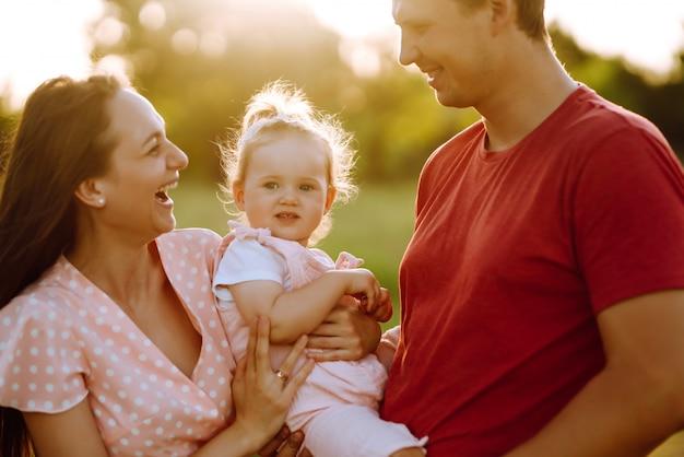 Счастливая молодая семья гуляя в парк на заходе солнца. мама, папа и маленькая дочь с удовольствием в парке летом. концепция счастливой семьи. родители держат ребенка за руки. поцелуи и объятия.