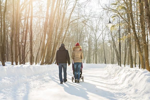 Счастливая молодая семья, прогулки в парке зимой. родители несут малыша в коляске по снегу.