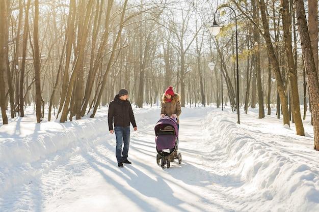 Счастливая молодая семья, прогулки в парке зимой.